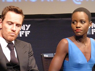 Lupita Nyong'o - Nyong'o and co-star Michael Fassbender at an event for 12 Years a Slave (2013). Her performance in the film earned her the Academy Award for Best Supporting Actress.
