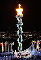 Interwoven steel frame several stories high with the lit flame at the top