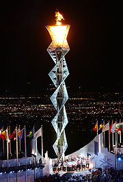 Opening ceremonies climax with the lighting of the Olympic Flame. For lighting the torch, modern games feature elaborate mechanisms such as this cauldron-spiral-cauldron arrangement lit by the 1980 U.S. Olympic ice hockey team at the 2002 Winter Olympics.