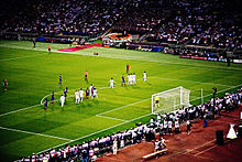 A wide-angle photograph of several football players preparing for a free-kick to be taken.
