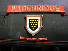 A 'West Country' class enamelled metal nameplate and shield mounted on flat metal casing covering the locomotive boiler. The nameplate comprises a scroll, and below this is a shield containing a picture of a coat-of-arms. A second scroll is below the shield, allowing identification as a member of the 'West Country class'.