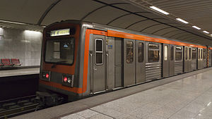 Grey subway train with orange stripe in a station