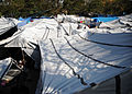 A group of temporary shelters made out of plastic sheeting and tarps are shown in Petionville, Haiti 100222-N-HX866-004.jpg