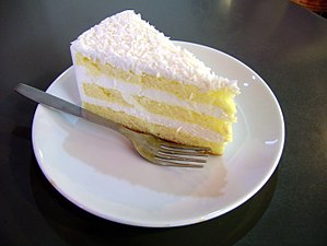 Photo of slice of coconut layer cake with white frosting on a white plate with dinner fork