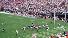 American football players line up in a goal line formation on an American football field surrounded by crowded stands.