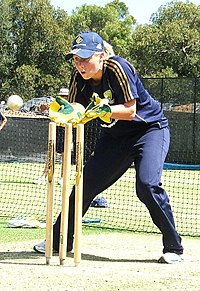 Young woman with a short blonde ponytail wearing a dark blue T-shirt, baseball cap and trackpants with gold stripes. Advertising logos of Adidas and Commonwealth Bank are present on the clothes. She is wearing gloves, standing with bent knees and open hands next to cricket stumps watching carefully for a white ball to catch.
