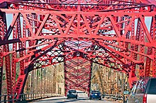 A red steel bridge arch seen from a car going under the metalwork along the bridge deck