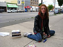 Photograph of a woman with facial lesions, sitting on the sidewalk
