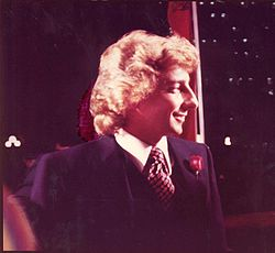 A man with long blond hair wearing a jacket and tie