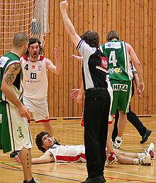 En dommer med armen løftet ved siden af en spiller på jorden.