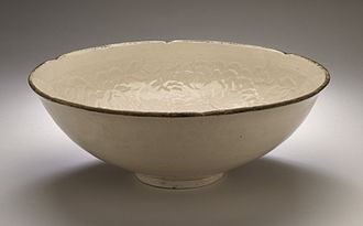 "Ding ware - Bowl (Wan) with Peony, Chrysanthemum, and Prunus Sprays, described by  LACMA as ""wheel-thrown stoneware with impressed decoration, transparent glaze, and banded metal rim"", though others would call it porcelain. 12th century"