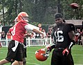 Brandon Weeden throwing, Josh Cribbs walking.jpg