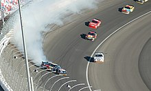 A car spinning sideways with white smoke coming from its rear-end