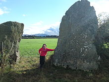 Bryn Gwyn stones, small adult leaning on slab stone, 11102009.JPG