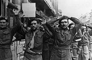 Soldiers surrendering some with their hands in the air other with them on their heads