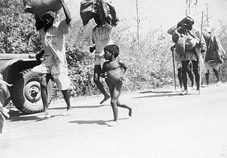 A small, naked, pot-bellied boy runs beside a line of men carrying large bundles on their heads. Some of the men are also running. All are on a road. A military vehicle is partially visible beside them.