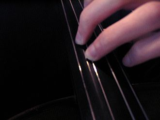 Bowed string instrument extended technique - A cellist performing a buzz pizzicato. Note the fingernail placed parallel to the string.