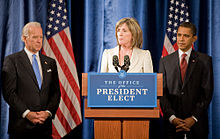 "A pale-skinned man in his sixties with white hair, a pale-skinned woman in her fifties with light brown hair, and a brown-skinned man in his forties with dark hair, all stand in front of a blue drape backdrop with two American flags. Both men are wearing dark business suits with white shirts and ties, one blue, one red; the woman is wearing a light beige suit jacket. The woman is behind a brown podium with a blue and white sign saying ""Office of the President Elect"" and two black microphones. All three are looking serious and both of the men have their hands folded in front of them."