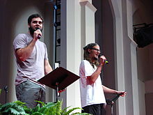 A photograph of two men with facial hair wearing t-shirts while speaking into black handheld microphones and gripping black music stands indoors