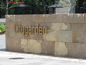 "The word ""Citygarden"" in gold metal letters is fixed to a low wall made of golden-yellow rock bricks."