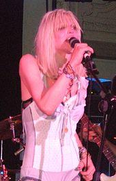 Um músico feminino, Courtney Love, que canta em um microfone em um concerto.  Ela está vestindo um espartilho lingerie e tem longos cabelos loiros.