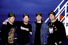 Four members of a rock band, Creed, are standing together. They are all wearing black sweatshirts. Three have goatee-style facial hair. Three have piercings.
