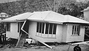 Black and white photograph of a contorted single-story home; a crushed automobile is visible beneath the structure