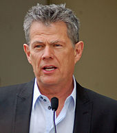David Foster speaking in front of a microphone