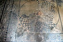 An ancient mosaic depicting the gorgon Medusa in the centre of a round geometric shield inscribed into a square also decorated with geometric motifs