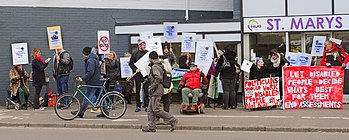 Disabled people protesting in 2015 against government policies and the inaccessibility of the assessment centre which has now been taken over by Maximus Inc. outside St Marys House, Norwich.