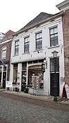foto van Huis met gepleisterde lijstgevel met in de kroonlijst kleine, ruitvormige vensters