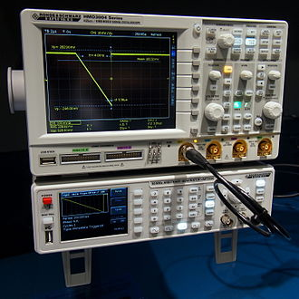 Arbitrary waveform generator - HAMEG HMF 2550 digital AWG under an oscilloscope displaying the generated waveform