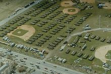 Aerial view of a large number of temporary housing tents positioned throughout several baseball fields