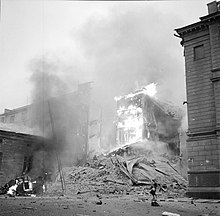 An apartment building is on fire and has partly collapsed in Central Helsinki after Soviet aerial bombing on 30 November 1939. A woman in a coat and a hat is passing by on the right next to the rubble and a car is on fire on the left.
