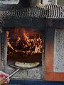 Flammkuchen wird in einen Holzofen geschoben.JPG