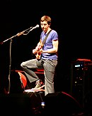 Gary Lightbody playing the guitar onstage, wearing a blue tee, striped pants and a pair of Converse