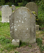 A granite headstone among other headstones
