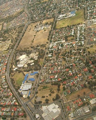 Gilles Plains, South Australia - Aerial image of western part of Gilles Plains, looking north. Grand Junction Road is the east-west road at the top, forming the northern boundary of the suburb. Sudholz Road, the north-south road at left, is the western boundary. To the north is Valley View. To the west is Oakden. The green and concrete rectangle to the top right is St Paul's College. The brown rectangle at the upper left is the Institute of Medical and Veterinary Science. The white-roofed complex to the south is a TAFE complex and the blue and white part further down is the Royal Society for the Blind. The white complex at the bottom is a shopping centre.