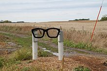 A sculpture consisting of two white posts holding a black spectacles frame in Buddy Holly's characteristic style