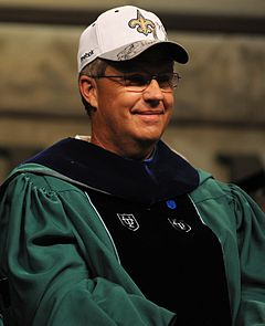 Photograph of Williams wearing a green and black Tulane University graduation gown and a white New Orleans Saints baseball cap