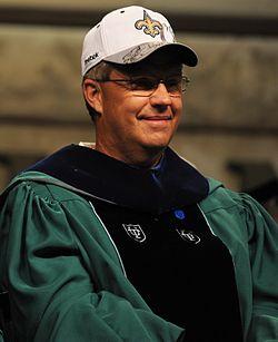 Foton de Williams portanta verdan kaj nigran Tulane University-diplomiĝrobon kaj blankan New Orleans Saints basbalan ĉapon