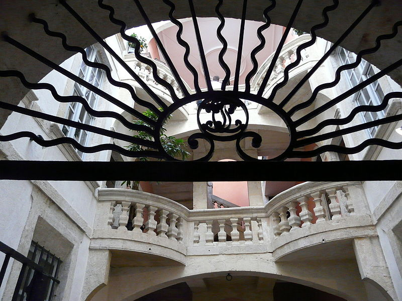 The Hotel Fontfroide entrance in Nimes, France. The top of the wrought iron gate with the stairs in the background.