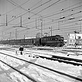 HUA-150925-Afbeelding van een electrische locomotief uit de serie 1100 van de NS met rijtuigen plan E op een besneeuwd emplacement bij het NS station Amsterdam C.jpg