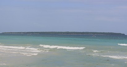 Long low green island, about 3.9km distant.  Two beaches can be made out.