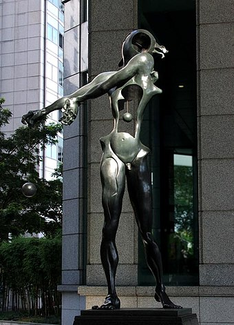 "Homage to Newton (1985), Bronze with dark patina. UOB Plaza, Singapore. Dali's homage to Isaac Newton, with an open torso and suspended heart to indicate ""open-heartedness,"" and an open head indicating ""open-mindedness"" Hommage a Newton.jpg"