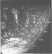 Black and white satellite image of a hurricane with an eye and well organized structure. Due to the storm's position near the edge of the image, most of the hurricane is not visible. The curvature of the Earth is visible on the right, and a coordinate grid with labels has been superimposed on the image.