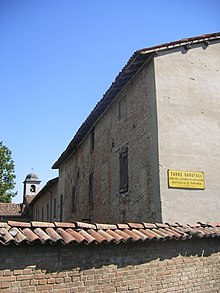 Edifício pequeno com um pátio rodeado por paredes de tijolos e uma torre sineira ao fundo.