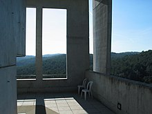 Two chairs on a concrete porch of a rectilinear building overlooking hills and green forest