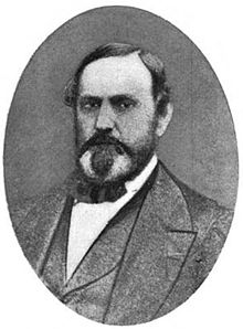 A man with receding black hair, sideburns, a mustache, and a goatee wearing a black jacket, vest, and bowtie, and a white shirt