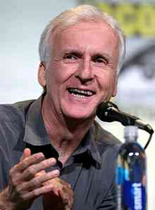 James Cameron, a man in his late fifties with white hair, smiling